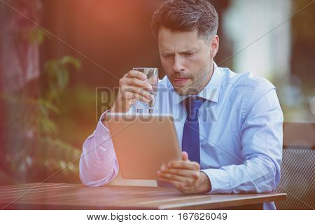Businessman drinking water while using digital tablet at sidewalk cafe