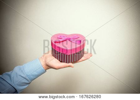 man holding a pink gift box in the form of heart