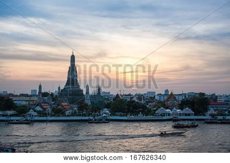 the temple of dawn with chao phraya river at dusk in bangkok thailand