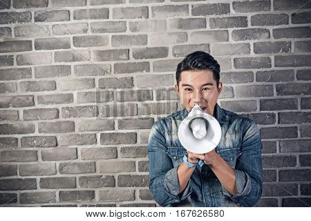 Asian young man hold a bullhorn against the gray brick wall