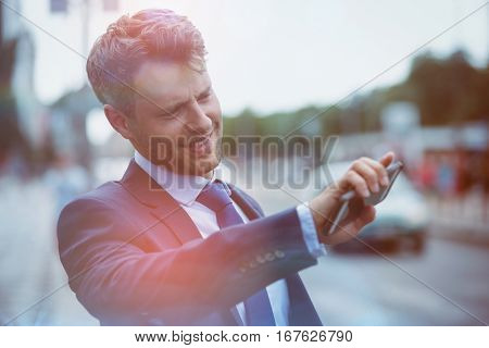 Handsome businessman holding mobile phone and hailing taxi at street