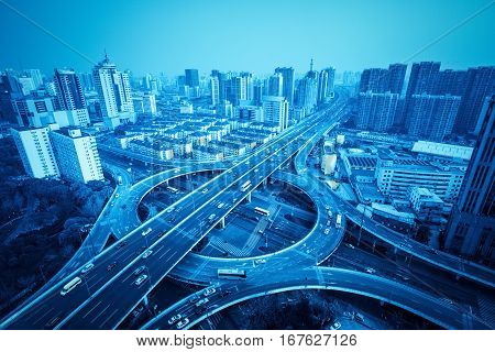 city overpass in shanghai with blue tone circular flyover and traffic light intersection
