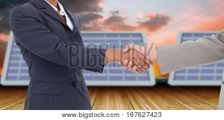 Side view of hands shaking against orange and blue sky with clouds 3d