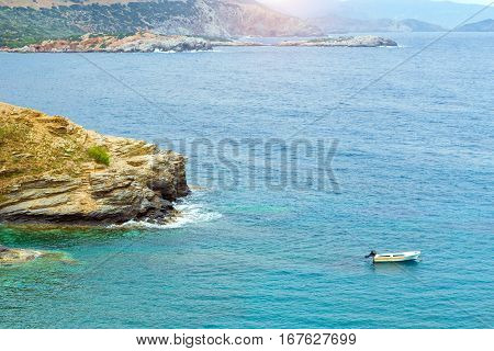 Empty motorboat drifting on waves near rocky shore. Sea view from cliff at foot of mountain and Bay separated by rocky stone ledges. Village Bali vacation destination resort. Rethymno Crete Greece