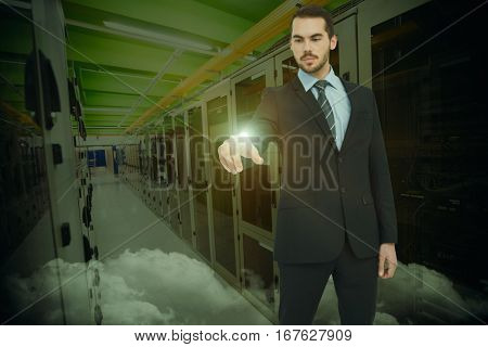 Cheerful businessman pointing at camera against image of data center