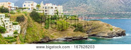 Waves near rocky shore. Sea view from cliff on resort architecture and excellent beach separated by rocky stone ledges. Village Bali - vacation destination resort. Rethymno Crete Greece
