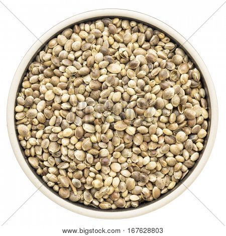 dried hemp seeds in a round bowl isolated on white