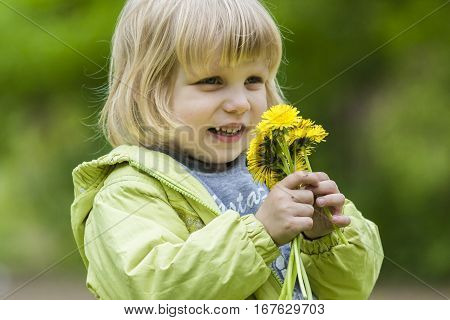 Close up portrait of smiling young girl holding bouquet of flowers in hands. Girl with yellow dandelions.