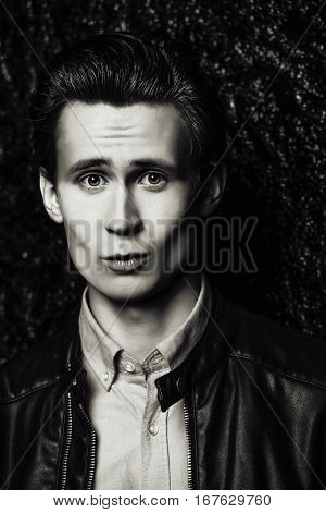 Black-and-white portrait of a funny young man looking at the camera with big eyes. Emotions.