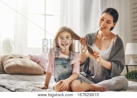 Happy loving family. Mother is combing her daughter's hair sitting on the bed in the room.