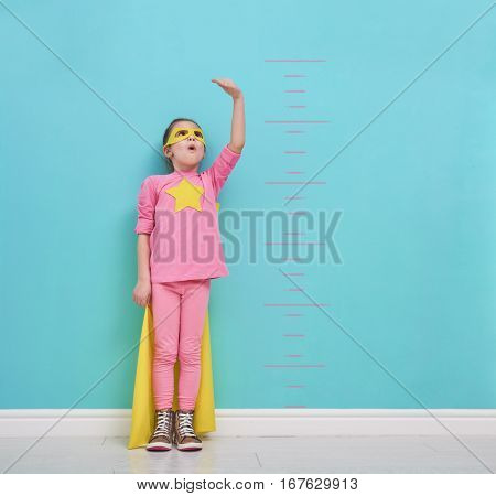 Little child plays superhero. Kid measures the growth on the background of bright blue wall. Girl power concept. Yellow, pink and  turquoise colors.