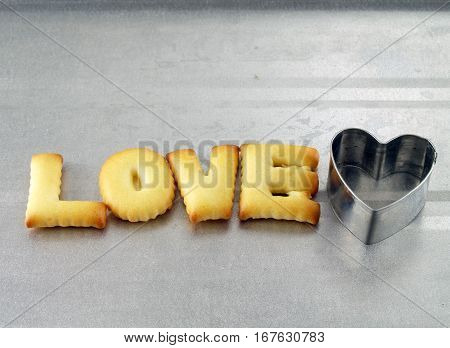 love word, closeup biscuit cookies letters with heart shaped cookie cutter on oven tray, snack for valentine's day