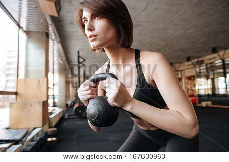 Beautiful young woman athlete working out with kettlebell in gym