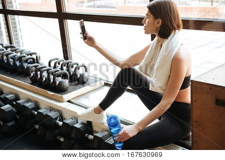 Attractive young sportswoman taking selfie with cell phone in gym