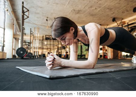 Focused young fitness woman doing plank exercise in gym