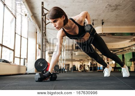 Attractive young woman athlete doing exercises with dumbbells in gym