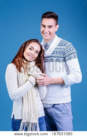 Winter, christmas and love concept. Happy man and woman in sweaters and scarf hugging and smiling to each other. Winter fashion.