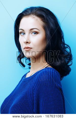 Portrait of a beautiful young woman with brunette hair over bright blue background. Beauty, fashion concept. Cosmetics, make-up. Copy space.
