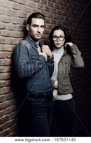 Portrait of a handsome young man and beautiful young woman standing against the brick wall. Beauty, fashion.