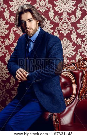 Fashionable male model in elegant formal suit posing in apartments with classical vintage interior.