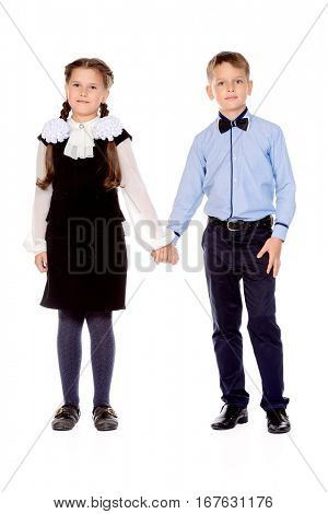 Portrait of two happy schoolchildren posing together at studio. School uniform. Education. Isolated over white.