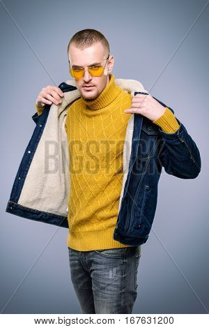 Sexual male model posing in jeans clothes and yellow sunglasses. Short hair styling. Studio fashion shot.