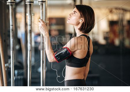 Serious young woman athlete working out and listening to music in gym