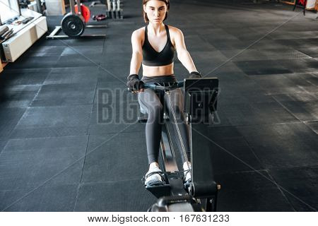 Serious young fitness woman exercising with training machine in gym