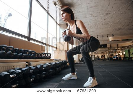Slim young sportswoman working our and doing squats with kettlebell in gym