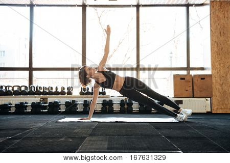 Serious young sportswoman doing exercises on mat in gym
