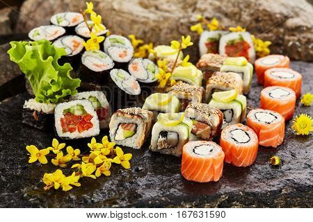 Japanese Sushi Set - Various Maki Sushi Roll on Black Stone. Japanese Cuisine and Natural Flower Concept