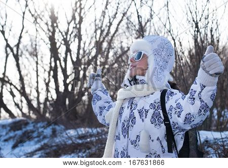 Happy little girl in winter clothes and sunglasses walking and having fun. Thumb up sign. Portrait of a beautiful fashionable little girl with sunglasses in the walking. Fashionable child.