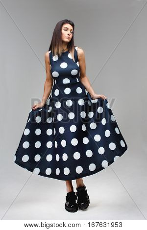 Girl demonstrates a dress in the peas with a large hem. Boho style model in studio wearing long blue dress with polka dots and big black boots. She is posing and looking aside