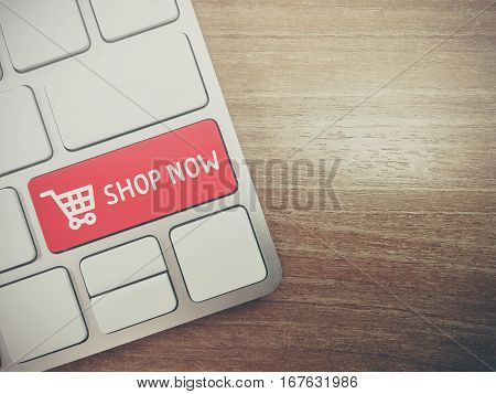 Computer keyboard with icon shopping cart word shop now on key. E-commerce concept