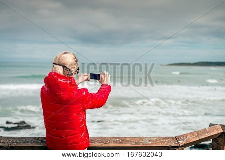Woman taking pictures of surfers with mobile phone Middleton South Australia