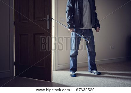 Burglar committing a burglary crime in a house with a crowbar