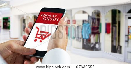 hand holding smartphone against sale advertisement
