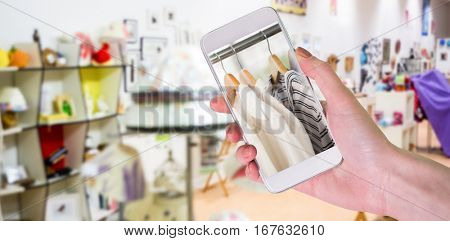 Hand holding smartphone against a shop