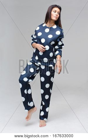 Model in dark blue polka dots pajamas staying in studio barefoot and looking aside. She has long brown hair