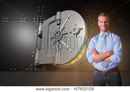 Smiling manager with arms crossed in warehouse against digitally generated half opened safe