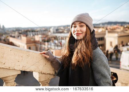 Happy attractive young woman walking in old city in spring