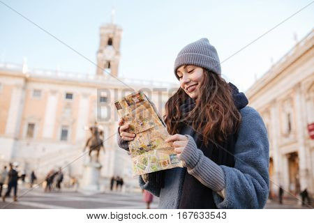 Happy cute young woman standing and using map in old city