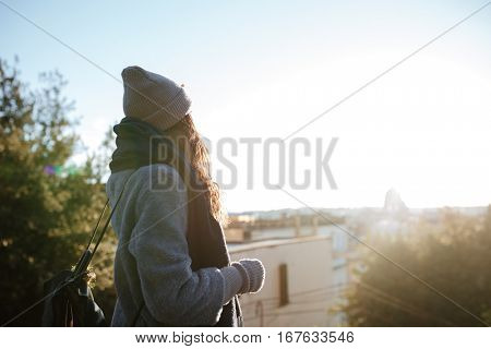 Back view of beautiful young woman enjoying the view on sunset in the city