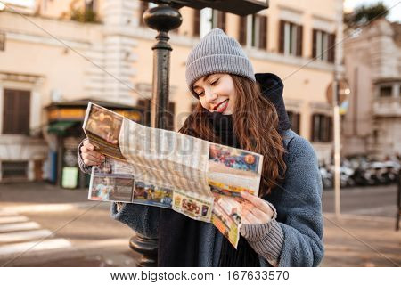 Smiling concentrated young woman using map and walking in the city