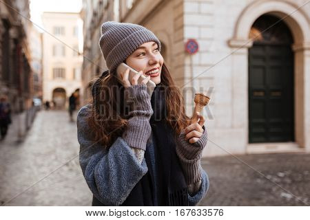 Happy lovely young woman with ice cream walking and talking on mobile phone in the city