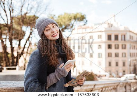 Cheerful attractive young woman using cell phone and map in the city