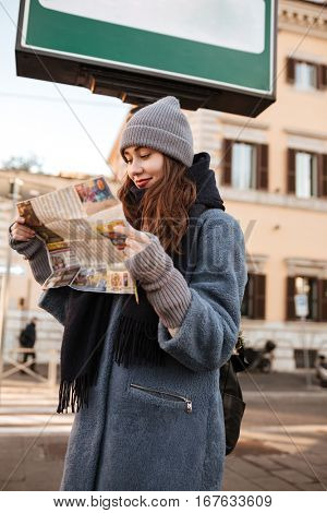 Pretty young woman tourist using map on the street of city
