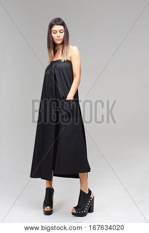 Nice young girl staying in the studio with grey background and looking down her hand in pocket, she wears in dark sexy long dress skirt and big shoes. Her hand is in the pocket.