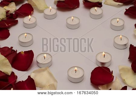 a heart of enlighted candlesa and rose petals