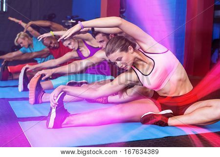 People doing stretching exercise while sitting in gym